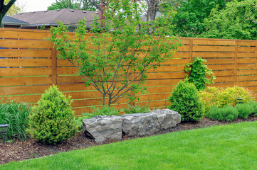 Foto op Canvas Tuin An Asian inspired and beautifully maintained garden features rockery and minimalist style cedar fencing.