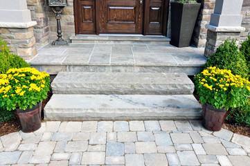 Flagstone applied to the original concrete veranda, natural stone steps, and paver walkway all provide a beautiful, fresh landscape update to this stately home.