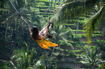Young woman swinging in the jungle rainforest of Bali, Indonesia