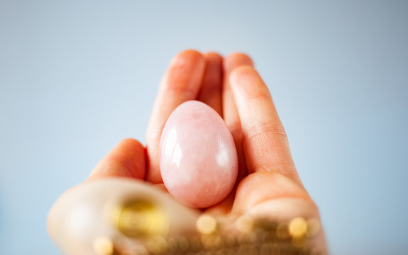 woman holding in hand a vaginal (yoni) egg. Rose quartz crystal jade egg. Copy space