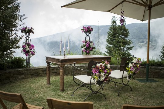 Table and two chairs with flower decoration on a garden over the mountains