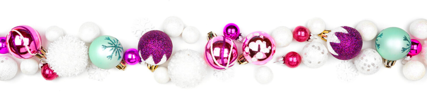 Christmas border of purple, pink and teal decorations. Top view isolated  on a white background.