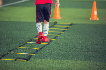 Back of kid soccer player Jogging and jump between marker for football training. Ladder drills exercises for football soccer team. Kid  wearing red sport shoes and exercises on ladder drills.