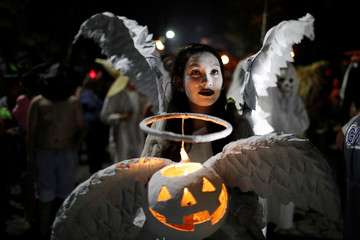 "A young woman dressed as an angel participates in a parade called ""La Calabiuza"" on the eve of the Day of the Dead in Tonacatepeque"