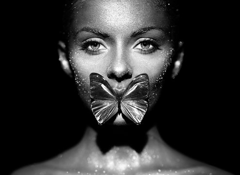 Fashion model woman in bright sparkles and lights posing in studio. Portrait of beautiful sexy woman with butterfly. Art design glitter glowing make up. Black and white photography