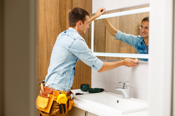 Man installing a mirror on wall in his renewed bathroom