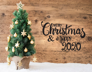 English Calligraphy Merry Christmas And A Happy 2020. Christmas Tree With Golden Ball Ornament And Snow. Brown Wooden Background