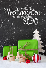 German Calligraphy Frohe Weihnachten Und Ein Glueckliches 2020 Means Merry Christmas And A Happy 2020. Green Christmas Present With Red Decoration And Snow, Tree And Reindeer, Snowflakes