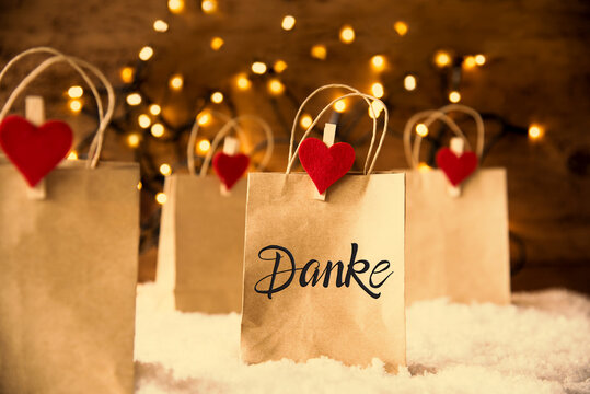 Christmas Shopping Bags On Snow With German Calligraphy Danke Means Thank You. Bright Glowing Lights In Background