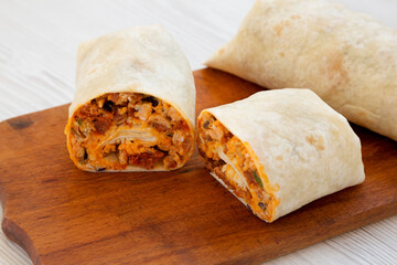 Homemade chorizo breakfast burritos on a rustic wooden board on a white wooden surface, low angle view. Close-up.