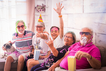 Party carnival or birthday leisure activity at home for mixed generations caucasian people family having fun al together -grandfathers and grandson in youthful crazy celebration