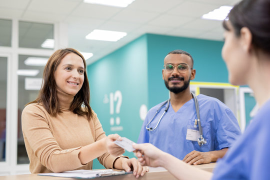 Patient giving credit card to receptionist in clinics to pay for medical service