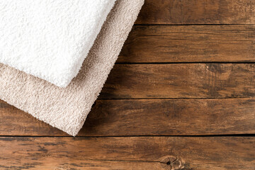 Stack of clean spa towels on rustic wooden background with copyspace. Top view