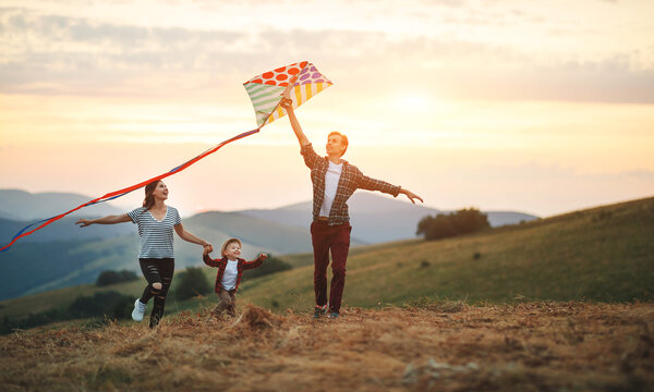 Happy family father of mother and child son launch a kite on nature at sunset.