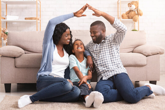 Black family making symbolic roof of hands above little girl