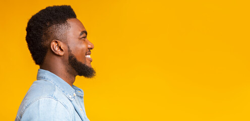 Profile portrait of cheerful bearded black guy on yellow background