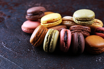 Foto auf Leinwand Macarons Sweet and colourful french macaroons or macaron on dark black background, Dessert.