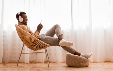 Man In Earphones Using Cellphone Sitting On Chair At Home