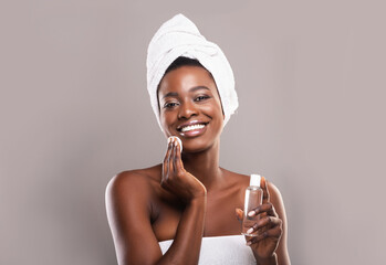 Fototapete - Black woman cleaning face with cotton pads and micellar water
