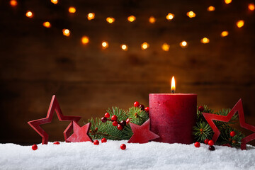Christmas or advent candle, fir branches, berry and red stars in snow against light  garland...