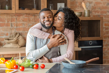 Portrait of lovely black couple embracing at kitchen