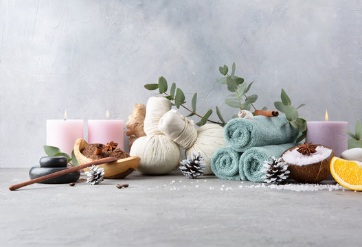 Beautiful winter spa relax concept. Coffee with cinnamon scrub, cotton pouches with herbs for massage, sea stones, eucalyptus and other Spa accessories on grey table.