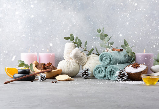 Beautiful winter spa with snow concept. Coffee with cinnamon scrub, cotton pouches with herbs for massage, sea stones, eucalyptus, honey, ginger, cones and other Spa accessories on grey table.