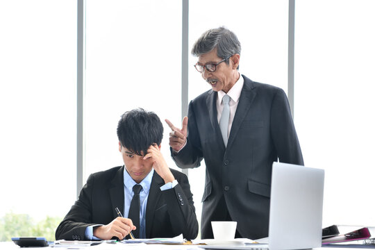 Angry boss yelling at employee, business concept, Asian businessman