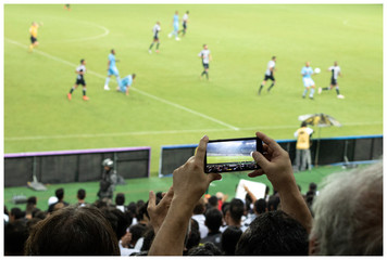 Man recording a soccer match on Brazil with his mobile phone