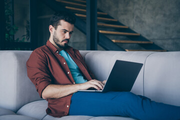 Profile photo of handsome guy holding notebook on knees freelance worker cosy lying sofa in living...