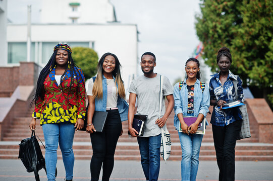 Group of five african college students spending time together on campus at university yard. Black afro friends studying. Education theme.