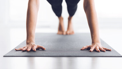 Slim woman practicing yoga in Plank pose, closeup