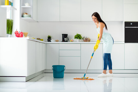 Profile side full size photo of positive cheerful girl having mop washing floor wearing white singlet yellow rubber gloves dotted apron fell content enjoy household chores in kitchen house indoors
