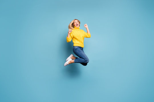 Full length profile photo of crazy lady jumping high celebrating winning free trip abroad rejoicing wear knitted yellow pullover jeans isolated blue color background