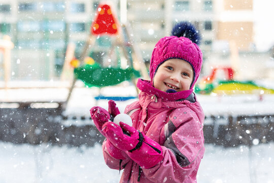 Cute adorable caucasian little girl winter portrait holding snowball in hands ready for snow fight at playground outdoor. Funny playful child during snowfall at cold season outside. Happy childhood
