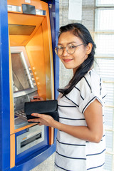 Fototapeta A young smiling woman with wallet standing by ATM and looking to camera. Asian girl is withdrawing money from ATM on the street.