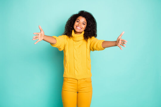 Photo of amazing dark skin lady with open arms waiting best friend coming for hugging wear yellow knitted pullover trousers isolated blue teal color background