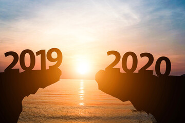 Silhouette of year 2019 to 2020 with sun rise on mountain and sea. Starting of new year concept. (defocused)