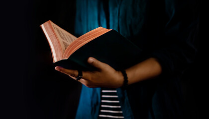 Reading Concept. Person Holding Opened Bible Book on Hand. Dark Tone, Cropped image