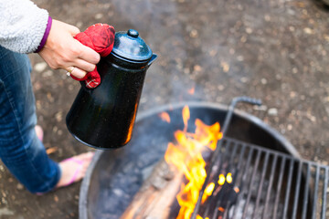 Woman holding placing tea water kettle on grill in fire pit at campground with red flame fire burning in evening or morning with mitten