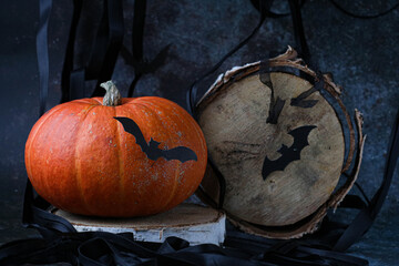orange pumpkin and black bats and wooden circle looking like moon on dark background. Halloween pic, vertical, side view