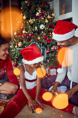 Happy parents with daughter in front of decorated Christmas tree have fun
