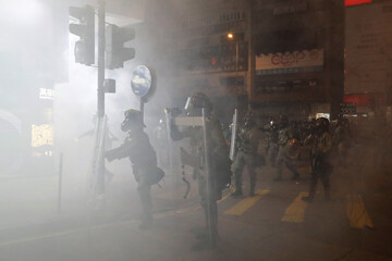 "Riot police stand inside a cloud of tear gas during a march billed as a global ""emergency call"" for autonomy, in Hong Kong"