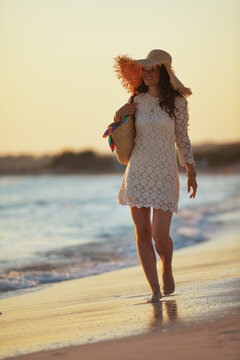 happy trendy middle age woman on ocean shore at sunset walking