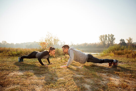 Fit young couple doing push-ups, facing each-other by the lake or river in early morning sunshine. Happy young man and woman exercising in the park