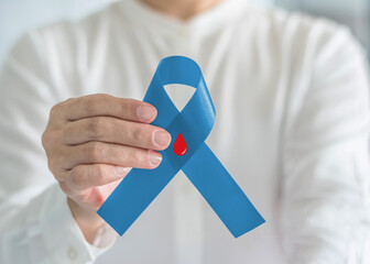 Diabetes Awareness ribbon for World diabetes day with red blood drop on blue bow color in person hand for supporting patient with diabetic disease