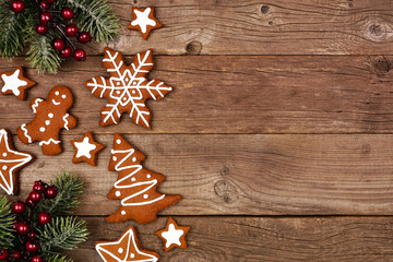 Wall Mural - Christmas side border of gingerbread cookies and tree branches. Above view on a rustic wood background with copy space.