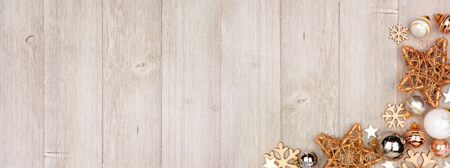 Wall Mural - Christmas corner border banner with white and gold ornaments. Above view on a gray wood background with copy space.