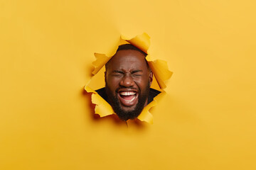 Happiness, ethnicity, fun and people concept. Headshot of black unshaven man laughs from joy, feels entertained, poses in ripped yellow background, has toothy smile, white teeth, jokes around