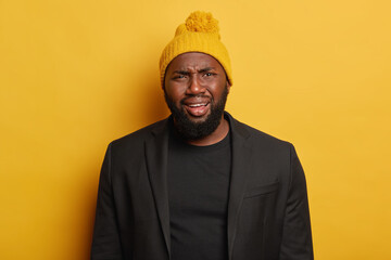 Grieved discontent black hipster man frowns face from dissatisfaction, wears yellow hat and black suit, gets unpleasant news, poses against yellow background. Negative human face expressions concept